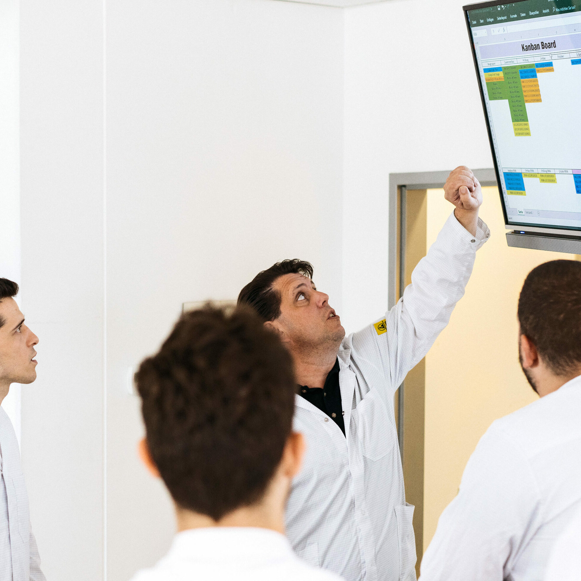 Stand-up meeting in front of an electronic Kanban board